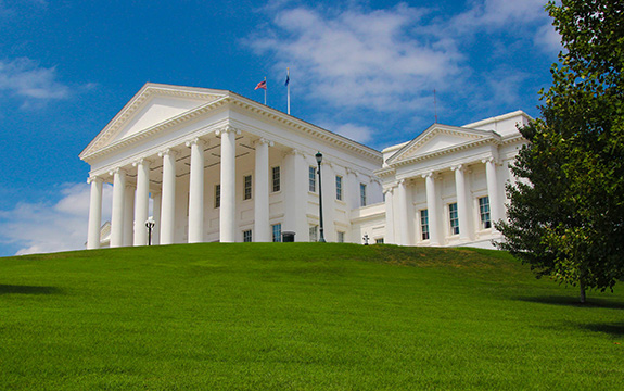 Caption: The Virginia State Capitol sits brightly white sandwiched between a bright blue sky and verdant green lawn., Credit: Matheus Gonçalves/Flickr