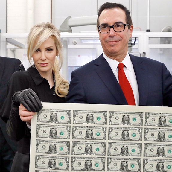 Caption: True man of the people and Trump Secretary of Treasury Steven Mnunchin poses with uncut dollars bills with wife Louise Linton, who is very approachable and down-to-earth and not at all a vapid out-of-touch .1%er., Credit: AP