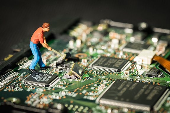 Caption: A small plastic statue of a man appears to smash a computer chip atop a green PCB., Credit: Preiser Project/Flickr