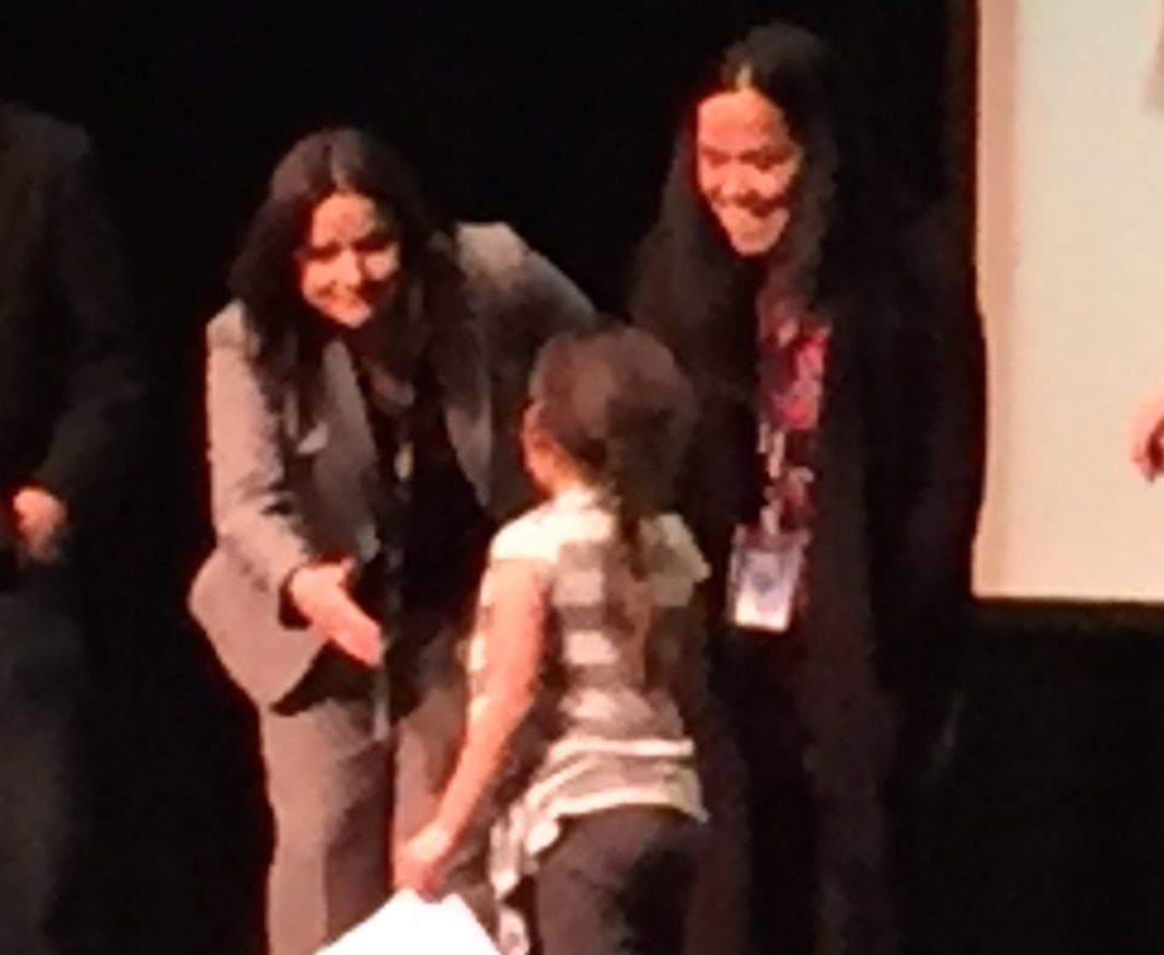 Caption: Danielle Grant congratulates a student at the Native families gathering in Minneapolis, Credit: Melissa Townsend