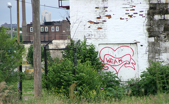 Caption: A red painted graffiti reading 'weak' adorns a white peeling plywood door in an old brick city building being consumed by nature., Credit: Paul Sabelman/Flickr