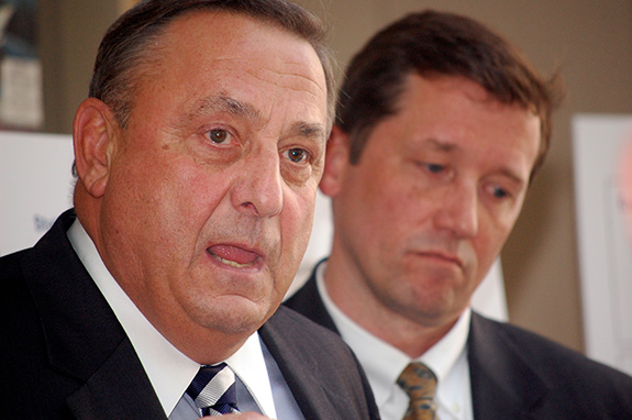 Caption: Maine governor Paul LePage speaks in a close up shot with a blurred out man in the background looking like a sad panda., Credit: Maine Department of Education/Flickr