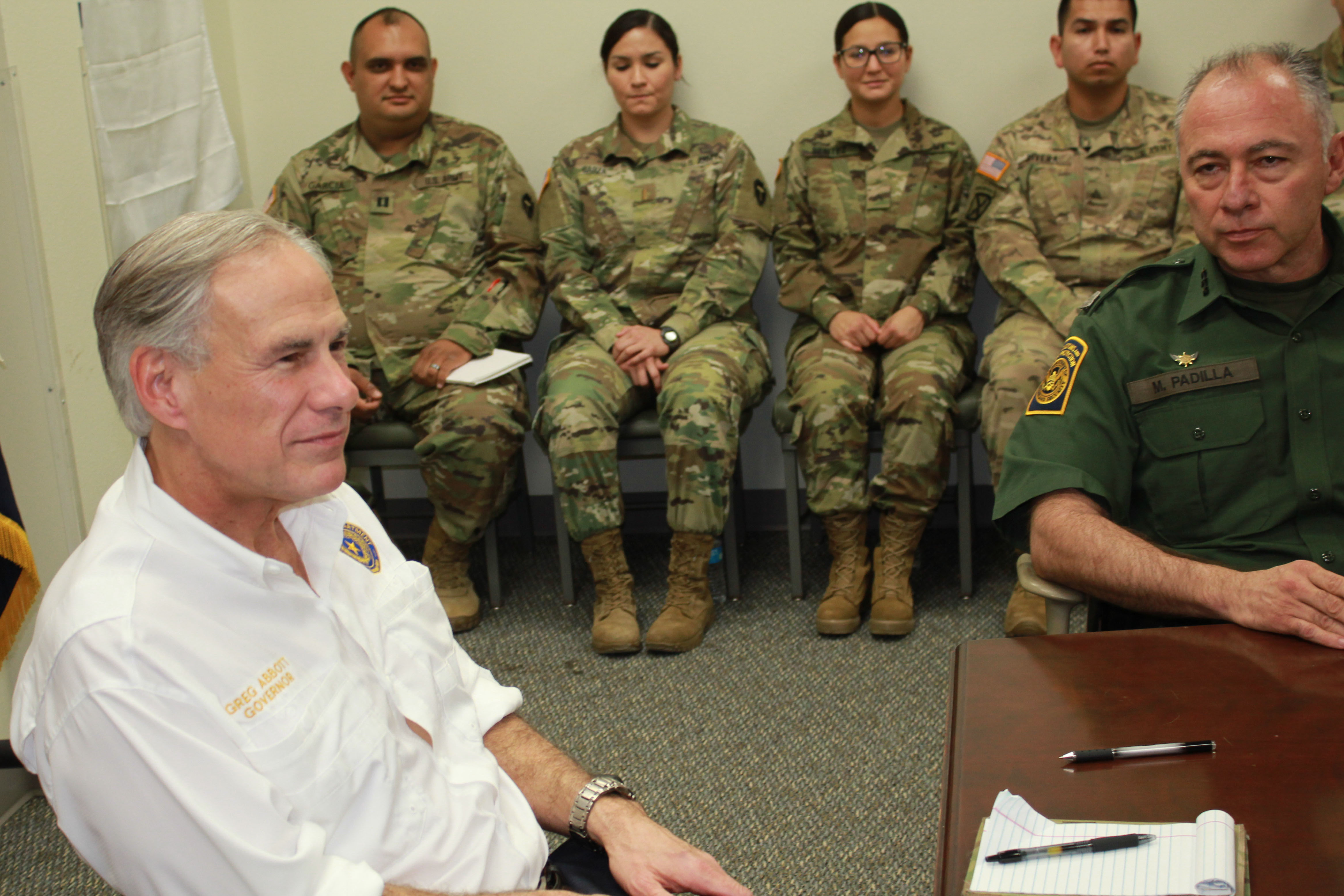 Caption: Texas Gov. Greg Abbott (left) and Manuel Padilla, chief of the Rio Grande Valley Border Patrol Sector, meet National Guard troops in Weslaco, Tex. , Credit: Carson Frame/American Homefront