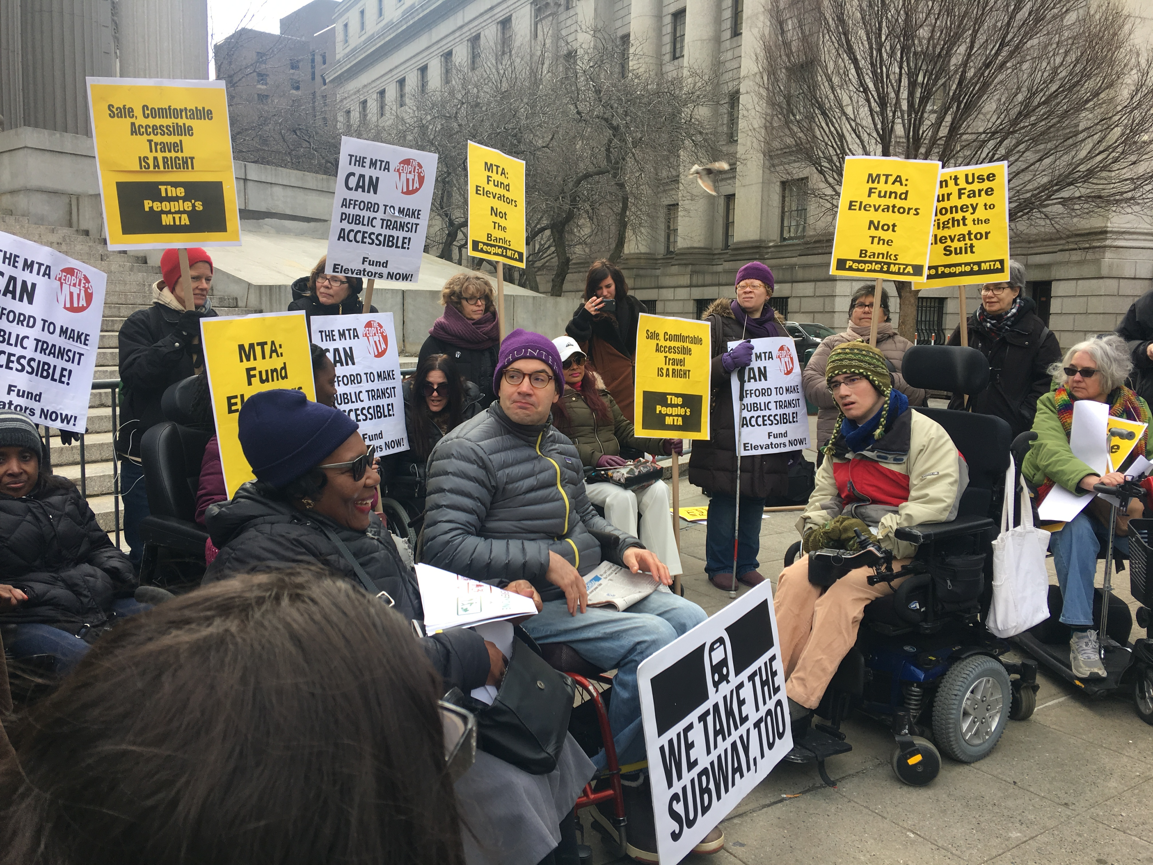 Caption: Disability rights advocates rally outside the Manhattan Supreme Court., Credit: Madeleine Thompson