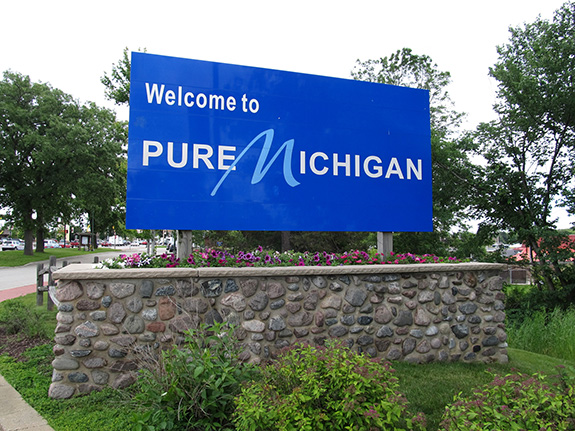 Caption: A bright blue sign reads 'Welcome to Pure Michigan'., Credit: Ken Lund/Flickr