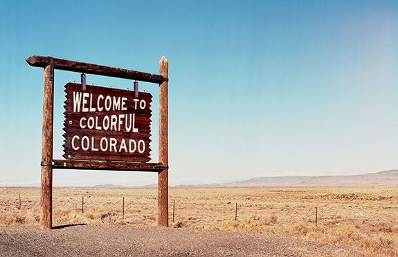 Caption: A pale blue sky sits above a brown wooden sign reading 'Welcome to Colorful Colorado'., Credit: ThoroughlyReviewed/Flickr