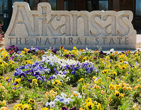 Caption: A stone carved sign reads 'Arkansas- A natural state' in front of a bed of flowers., Credit: BFS Man/Flickr