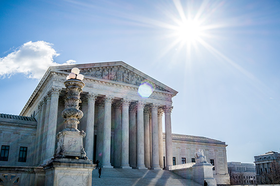 Caption: The U.S. Supreme Court building is seen from the front on a lightly clouded sunny day., Credit: Phil Roeder/Flickr