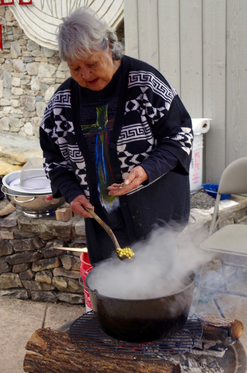 Caption: Martha Sherril prepares hominy over a wood fire outside the Museum of the Cherokee Indian, Credit: Carla Seidl
