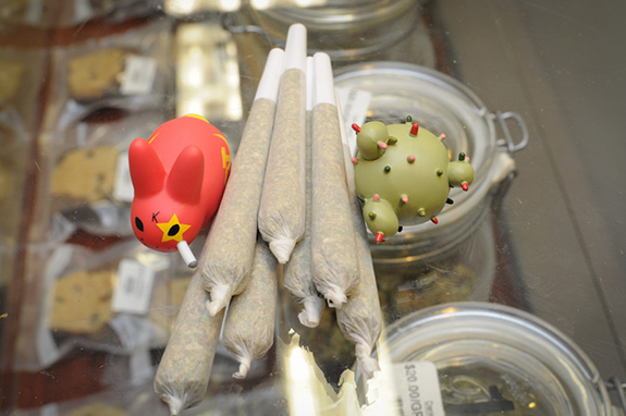 Caption: A cluster of pre-rolled joints sits stacked up between two little plastic cartoon figurines., Credit: Dank Depot/Flickr