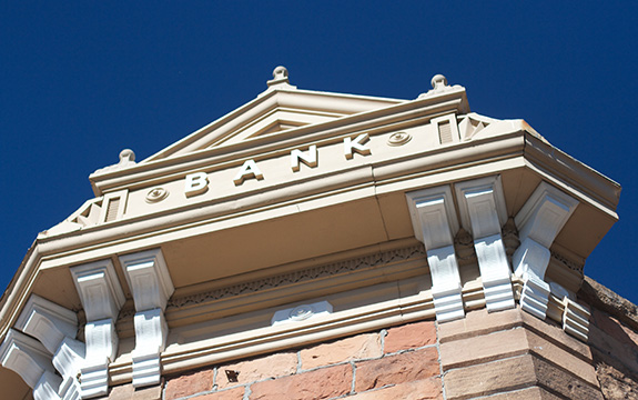 Caption: A stone building reading 'bank' is seen from below at street level., Credit: Alan Levine/Flickr