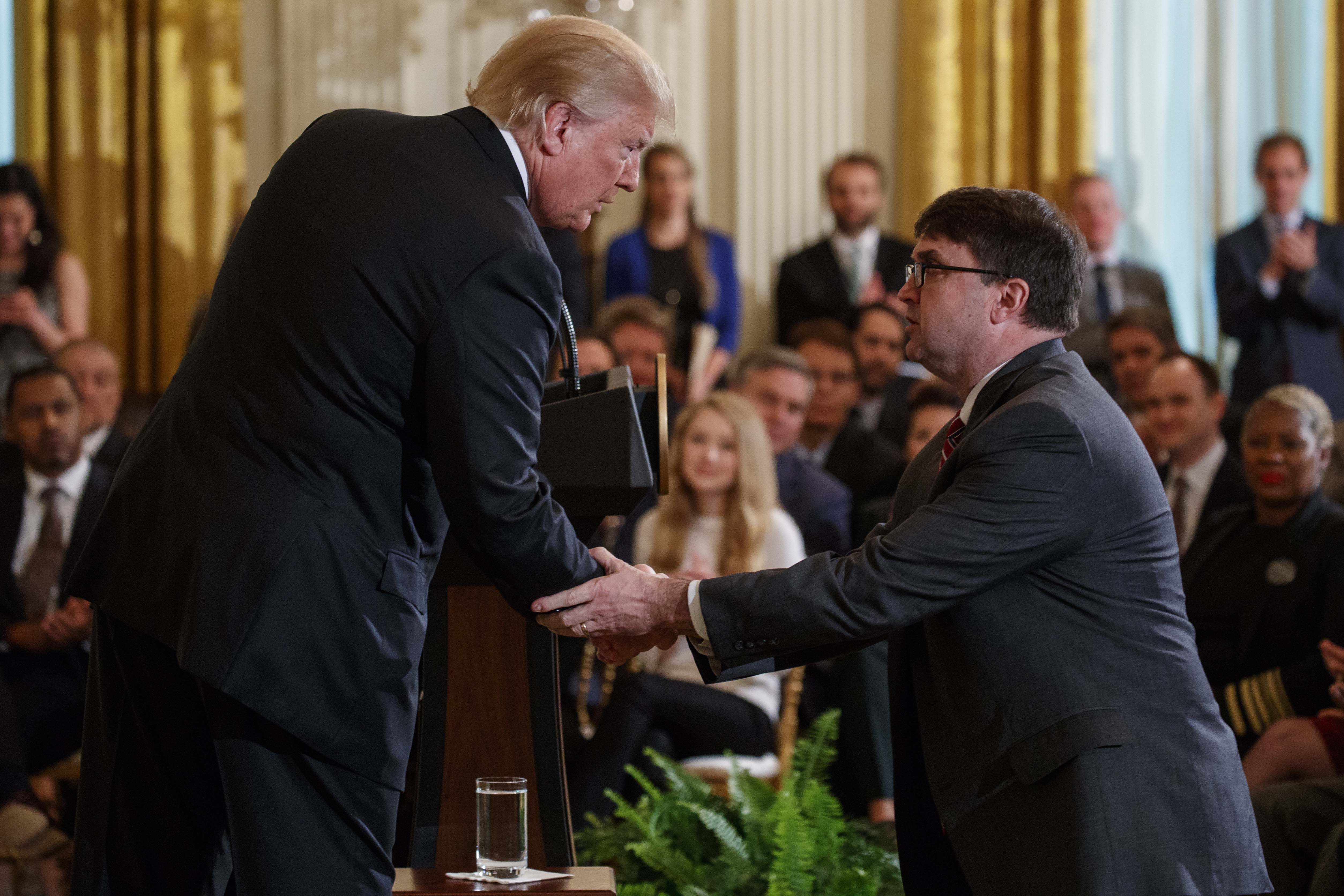 Caption: President Donald Trump shakes hands with acting Department of Veterans Affairs Secretary Robert Wilkie after announcing he will nominate him to lead the department during an event on prison reform in the East Room of the White House, Friday, May 18, 2018., Credit: Evan Vucci / AP