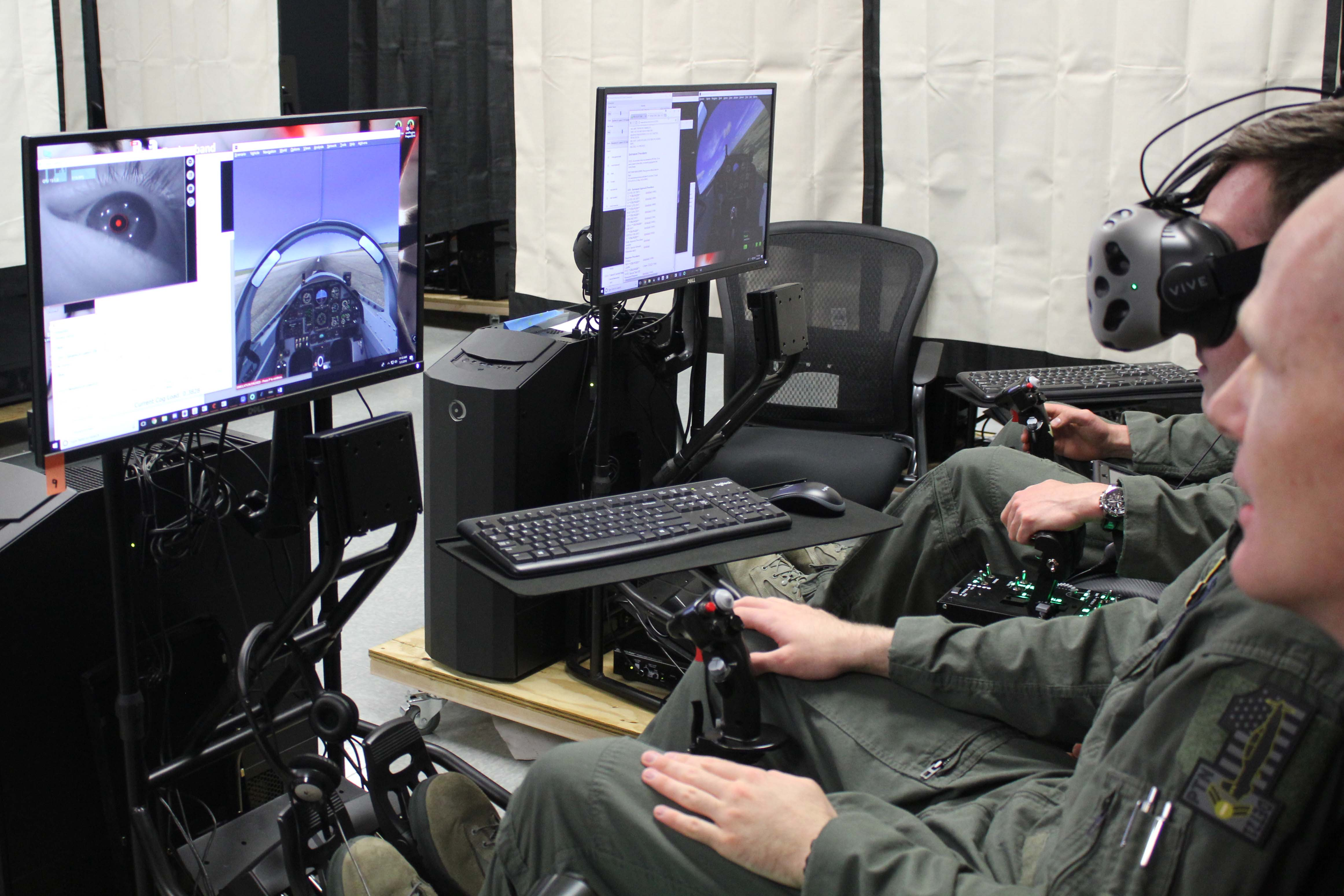 Caption: Airman 1st Class Jack Pepper (with goggles) attempts a maneuver on a simulator while Lt. Col. Paul Vicars looks on. Pepper is among the first participants in Pilot Training Next, which uses off-the-shelf virtual reality technology., Credit:  Carson Frame / American Homefront