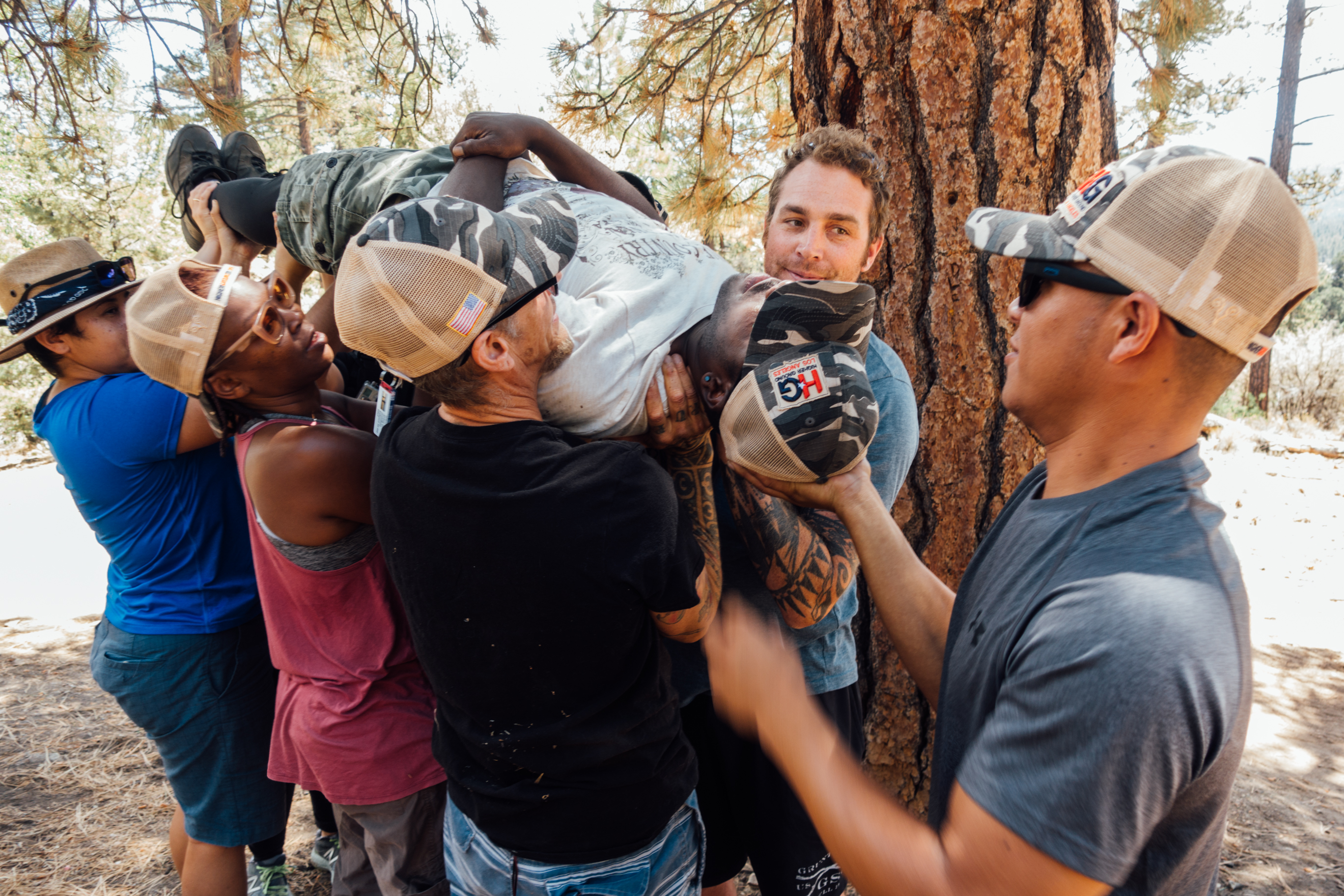 Caption: Jesus Guzmán (right) and fellow Higher Ground veterans participate in a team-building exercise during a hike in Big Bear, Cal., Credit: Libby Denkmann/American Homefront