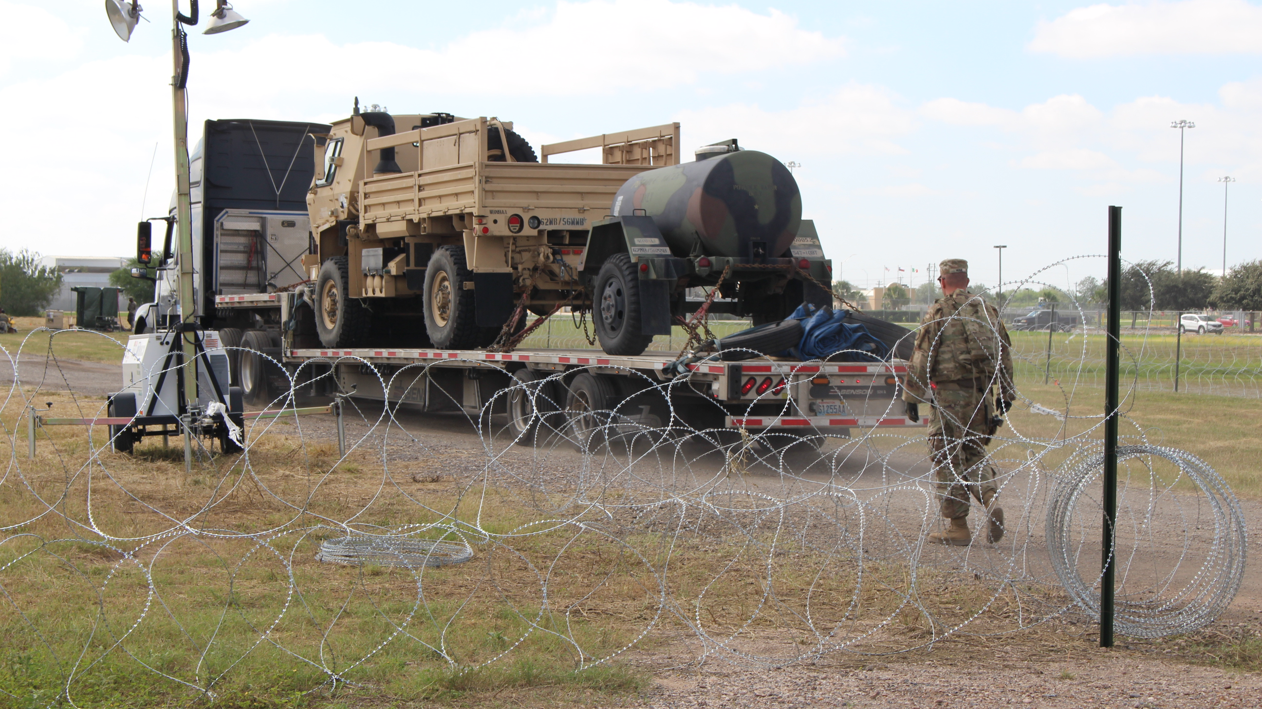 Caption: A military vehicle enters an encampment in Donna, Texas, just inside the U.S. border with Mexico., Credit:  Carson Frame / American Homefront