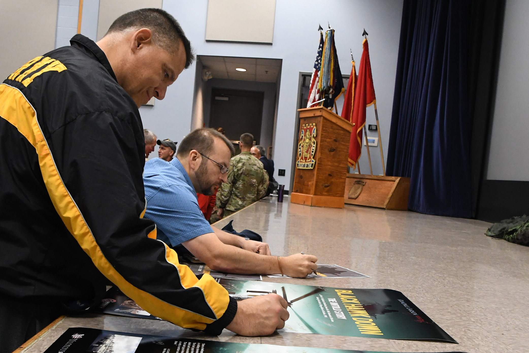 """Caption: Veterans sign the movie poster for """"Black Hawk Down: The Untold Story"""" at an October screening at Fort Drum, N.Y., Credit: Mike Strasser / U.S. Army"""