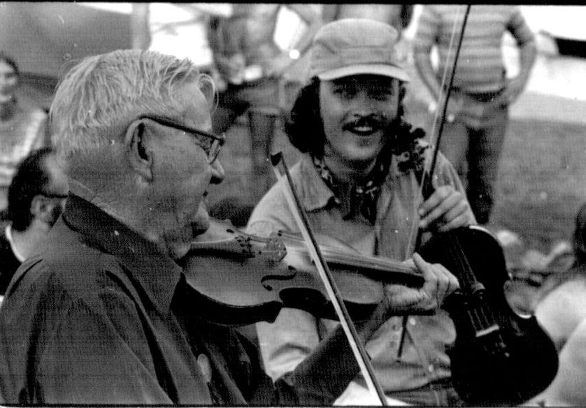 Caption: Bill Hicks (right) grins with joy as he observes North Carolina fiddle master Tommy Jarrell  at a fiddlers' convention circa 1972.  Hicks, a founding member of the Red Clay Ramblers and the Fuzzy Mountain String Band, passed away recently at age 75. We of, Credit: Paul Brown collection, courtesy Bill Hicks