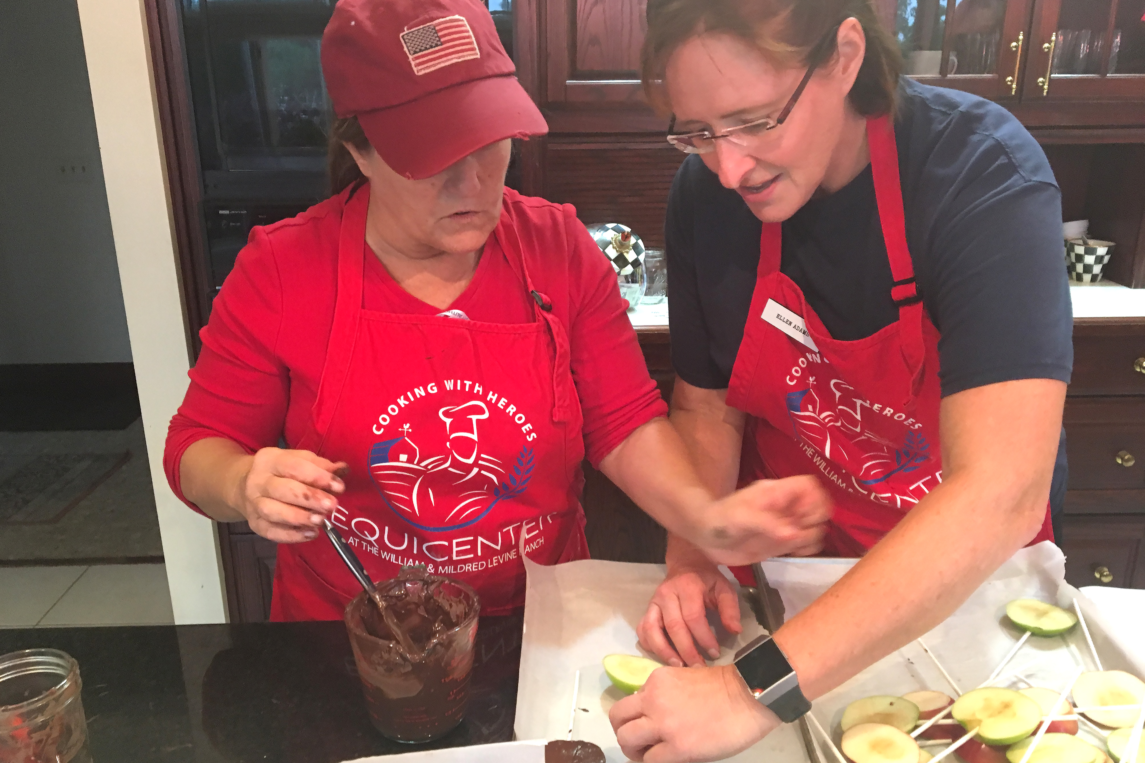 Caption: Chef Ellen Adams (right), an Air Force veteran, helps fellow veteran Linda Costello coat apples in chocolate., Credit: Sarah Harris/American Homefront