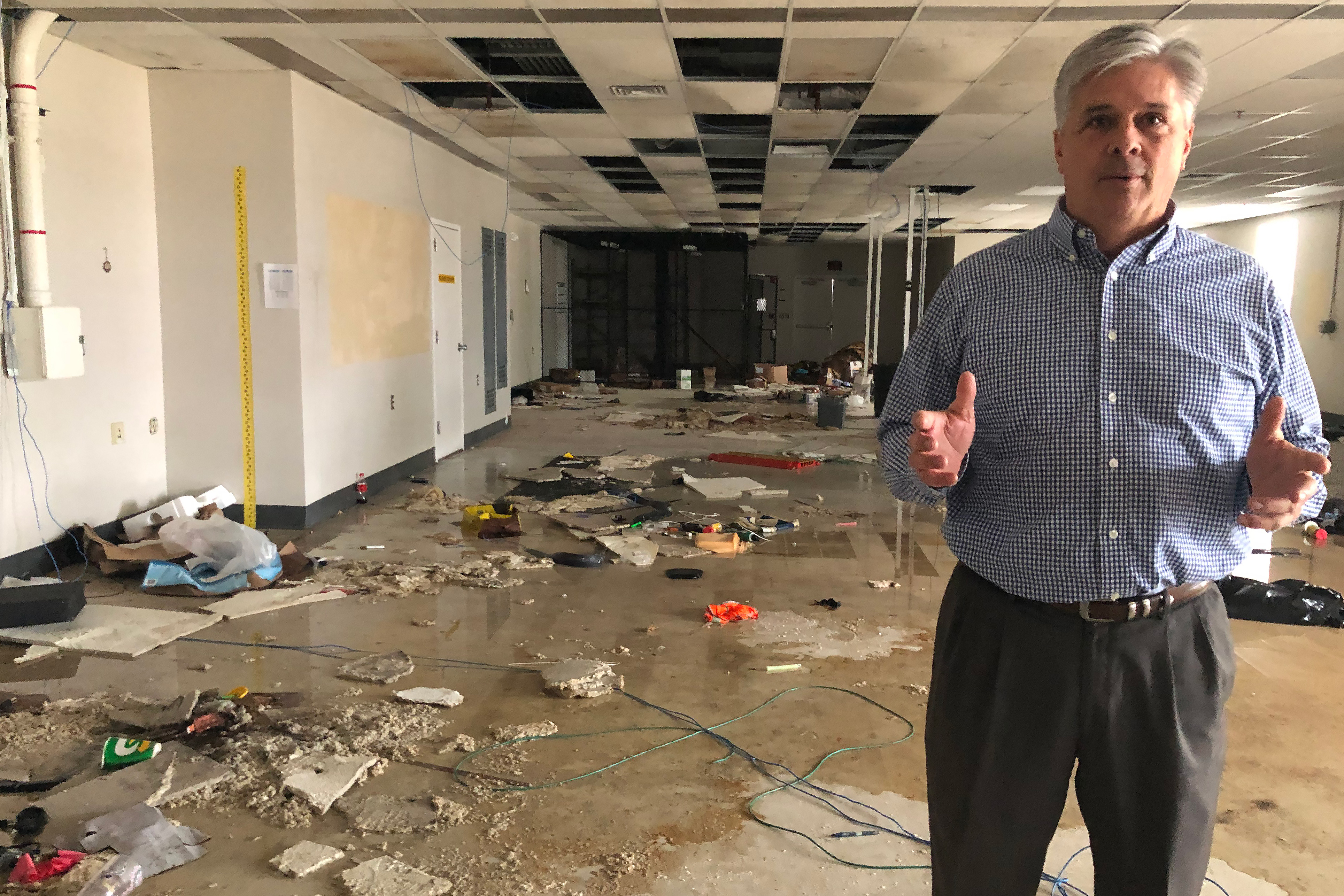 Caption: Tony Sholar of the Marine Corps stands in the abandoned headquarters of a Marine unit at Camp Lejeune. The building was damaged in Hurricane Florence, and rainwater still pours through damaged roof., Credit: Jay Price / American Homefront