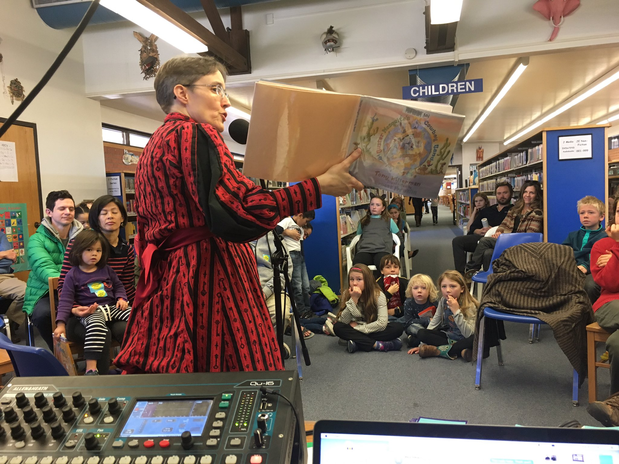 "Caption: Librarian Laura Metzler reads Tony Hillerman's ""Buster Mesquite's Cowboy Band"", Credit: Katie Stone"