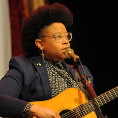 Caption: Amythyst Kiah on the WoodSongs Stage.