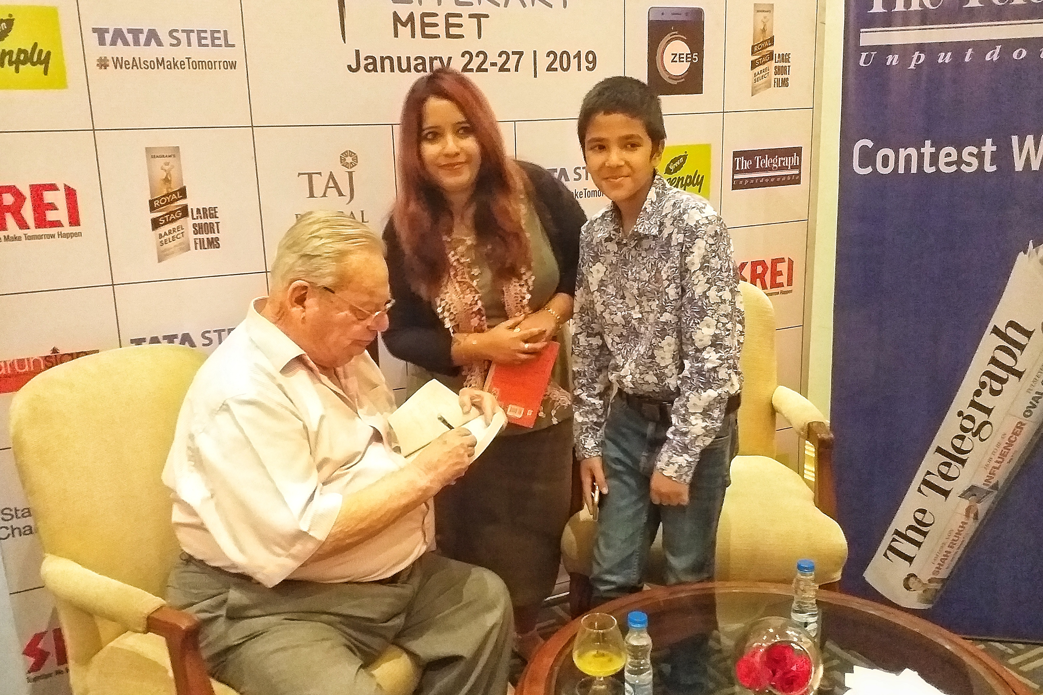 Caption: Ruskin Bond signing a book for a fan, Credit: Sandip Roy