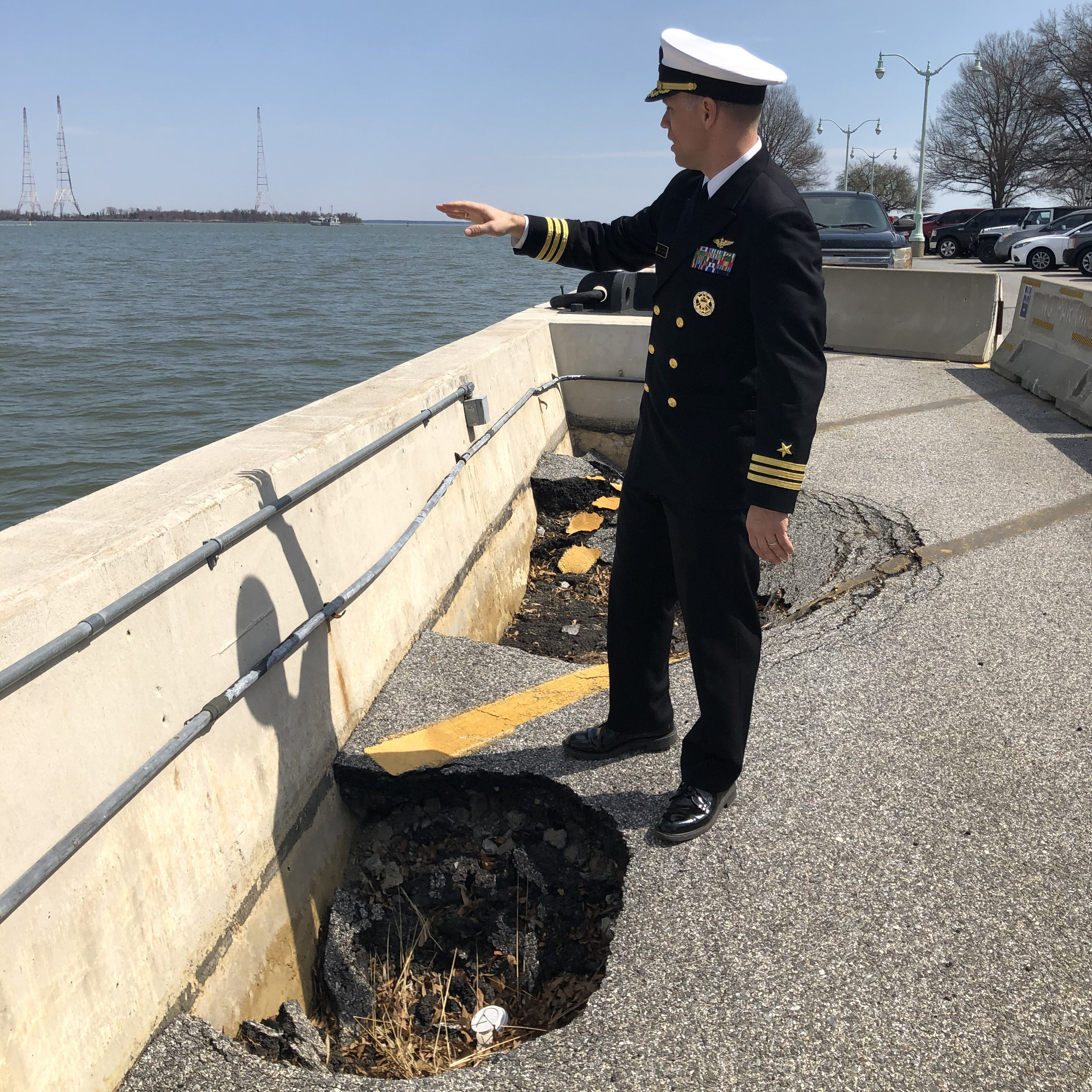 Caption: Commander David McKinney, a spokesman for the U.S. Naval Academy, stands alongside a sinkhole on the Severn River waterfront, where the Academy plans to build a new seawall to better withstand flooding., Credit: Jay Price/American Homefront