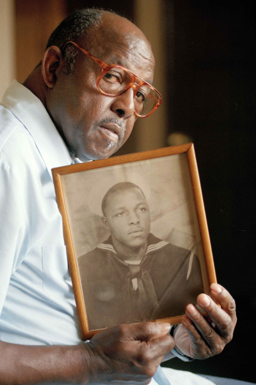 Caption: Freddie Meeks, sailor in the disaster at  weapons shipping depot in Port Chicago, Calif., holds a picture of himself as a young seaman  July 14, 1994. He died in 2003. , Credit: (AP Photo/Chris Pizzelo)