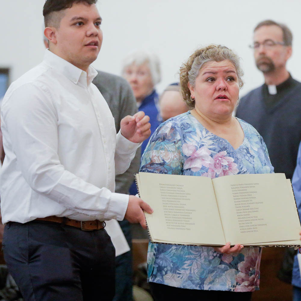 Caption: Pedro Lopez (left) stands beside his mother, Consuelo Lopez (right) in May of 2011 at St. Bridget Catholic Church on the 10th anniversary of the Postville raid. Consuelo is carrying the Book of Names — a record of those arrested and detained. , Credit: Photo by Jim Slosiarek of The Gazette, Cedar Rapids, IA.