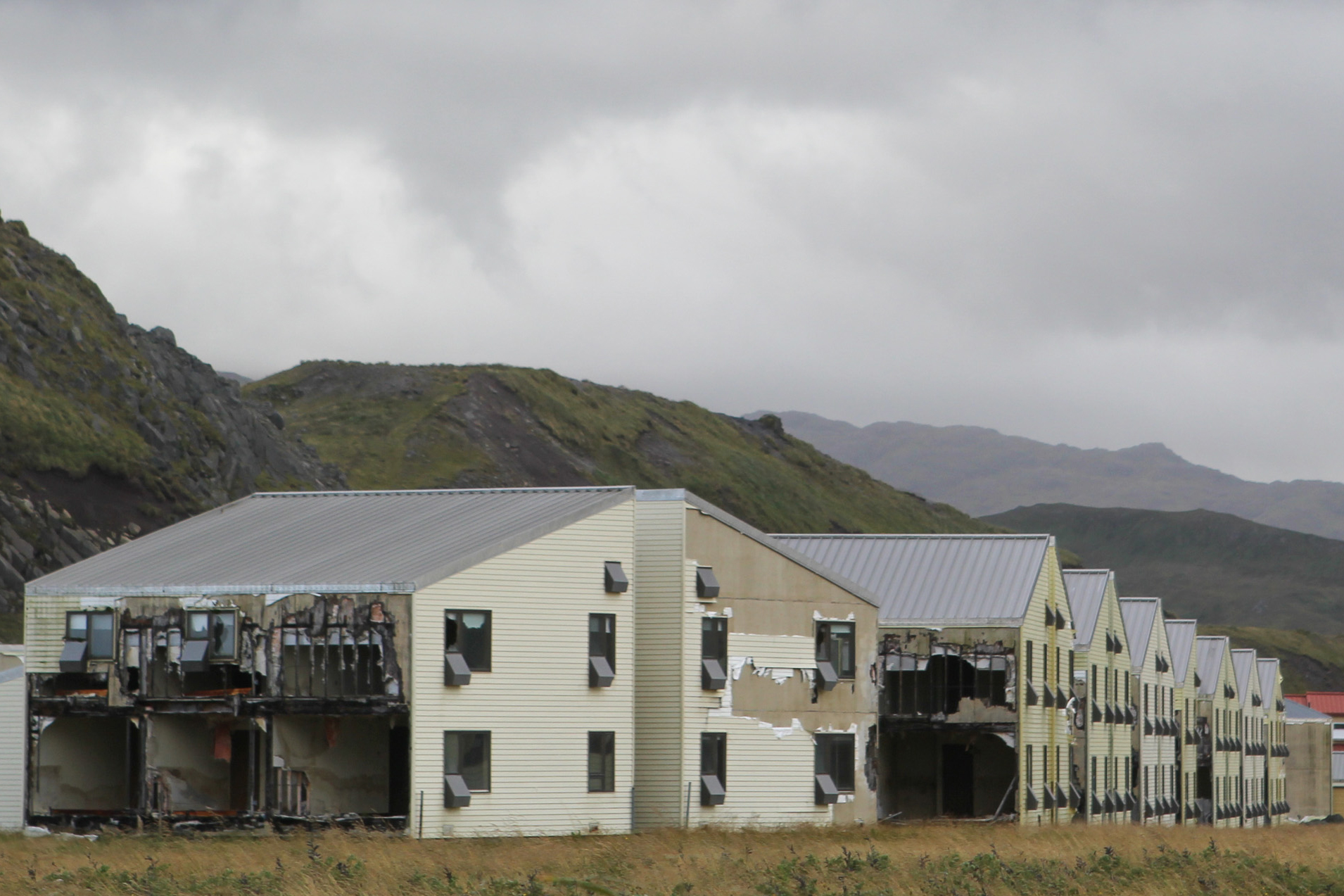 Caption: The military abandoned the Naval Air Facility Adak in 1997, and many of its buildings remain standing in disrepair. Some residents of the remote Alaska town hope a revived military interest in the Arctic will bring the military back., Credit:  Zachariah Hughes / Alaska Public Media