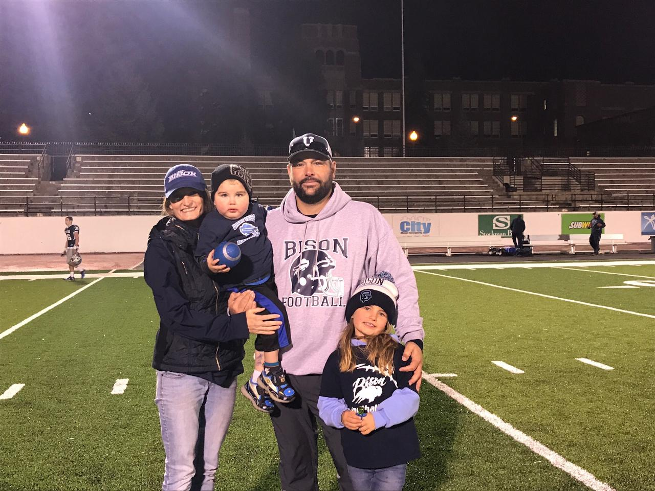 Caption: Wes and Callie Ross hold Troy with their daughter, Kennedy, at a football game.