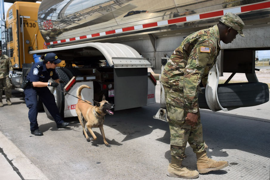 Caption: Spc. Afeez Amusan of the Texas Army National Guard, right, inspects a tractor-trailer alongside a U.S. Customs and Border Protection agent at the U.S.-Mexico border in Pharr, Tex., Credit:  Jon Soucy / National Guard Bureau