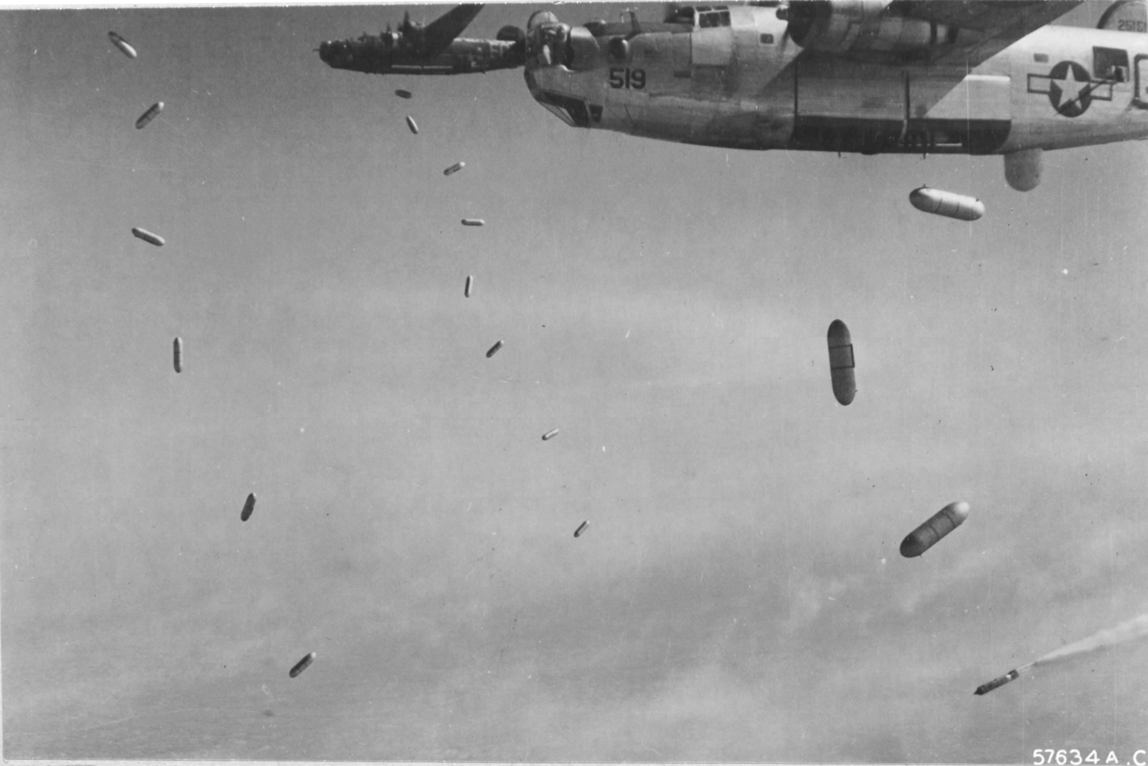 Caption: B-24J Liberators of the 579th Bomb Squadron drop incendiary bombs made from fighter plane drop tanks filled with napalm on targets near Royan, France, Apr 15 1945.