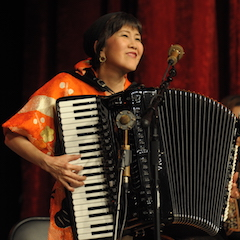 Caption: Accordion master Mihoko Goto on the WoodSongs Stage.