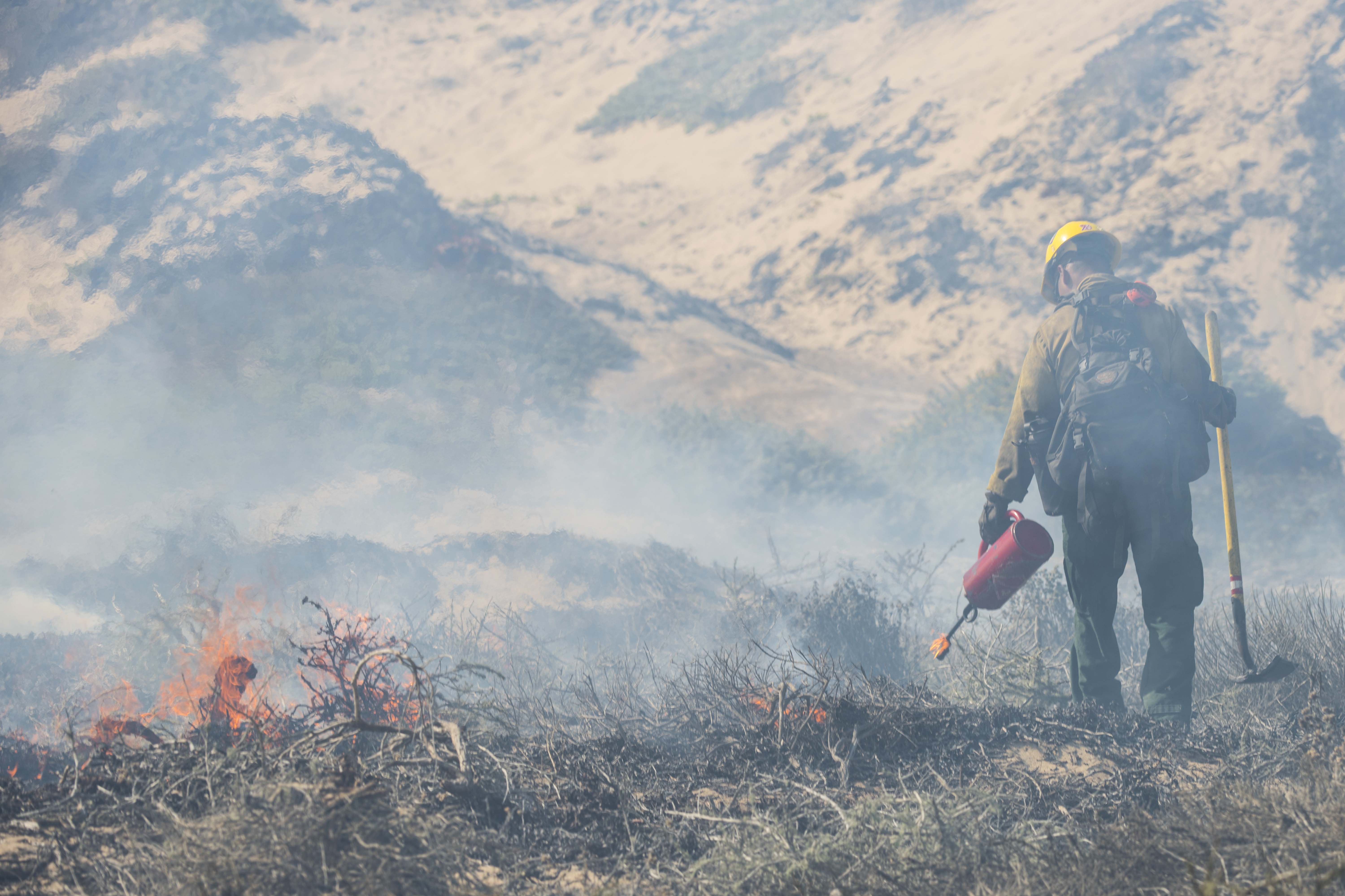 Caption: A fire fighter monitors a controlled burn Sept. 18, 2019 at Vandenberg Air Force Base, Calif. The burn was intended to reduce the risk of wildfires., Credit: Aubree Milks / U.S. Air Force