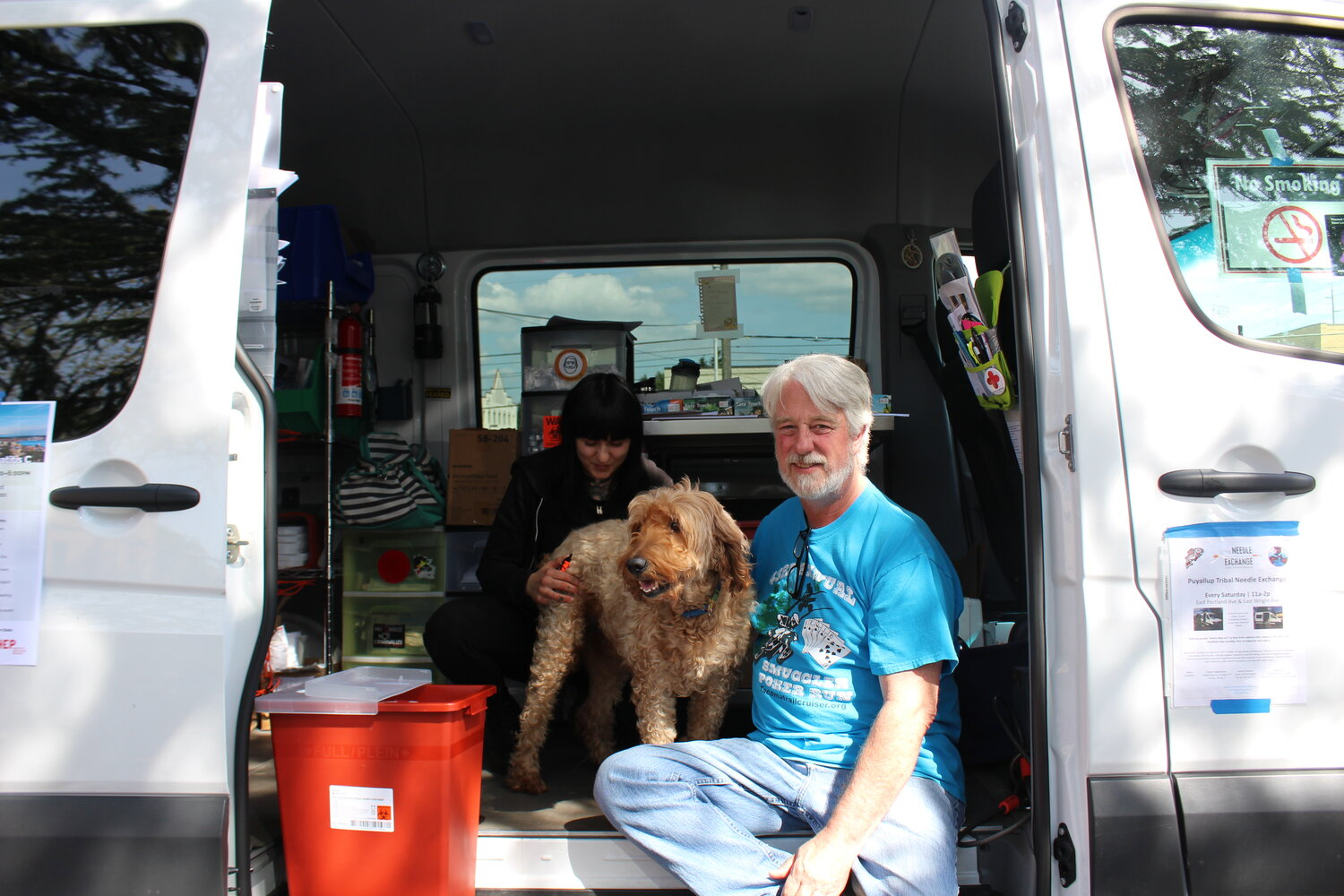 Caption: David Venes (right) poses at the Tacoma Needle Exchange van with his dog, Ethel, and outreach worker, Laura Reynolds., Credit: Amber Cortes