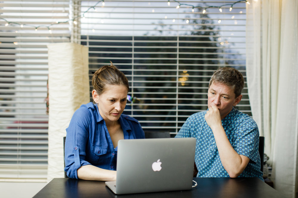Caption: Anna Boiko-Weyrauch (left) and Kyle Norris work on the first season of Finding Fixes at Anna's dining room table., Credit: Leah Nash for Finding Fixes