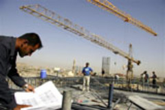 Caption: Cranes tower over a construction site in Irbil., Credit: Associated Press