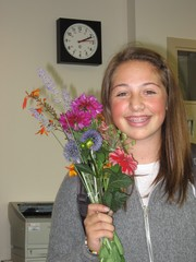 Caption: Molly holds up the flowers she picked while reporting from the Children's Garden at Seattle Tilth, Credit: Nathan Friend