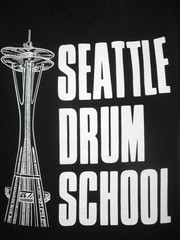 Caption: A t-shirt showing the logo of the Seattle Drum School. Artur Sapek hosted today's podcast live from the school to find out how musicians are being impacted by the recession., Credit: Artur Sapek