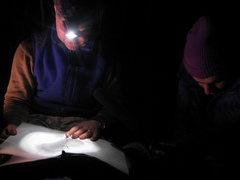 Caption: John Casteen reads a poem by the light of his headlamp., Credit: Greg Antrim Kelly