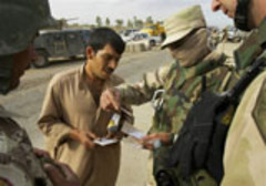 Caption: An Iraqi interpreter helps a US soldier to inspect a man's identity papers., Credit: AP Photo/Jacob Silberberg