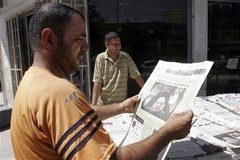 Caption: An Iraqi man reads a newspaper in Baghdad., Credit: Associated Press