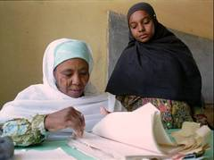 Caption: A Sudanese woman confirms the registration of a voter., Credit: Associated Press