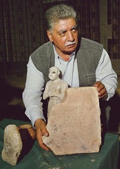 Caption: An Iraqi official displays a recovered stolen artifact., Credit: Associated Press