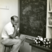 Caption: Rudolph Pariser in front of a blackboard with quantum calculations, contemplating molecular model, 1950s. , Credit: Courtesy of The Hagley Museum and Library.