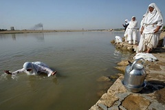 Caption: A Sabian Mandaean prepares for baptism in the Tigris., Credit: Associate Press