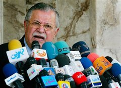 Caption: Iraqi president Jalal Talabani speaking to the press., Credit: Associated Press