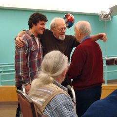 Caption: Mike Miller sings twice a week at the Hebrew Rehabilitation Center in Boston. At left is his grandson Ben.