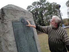 Caption: History Professor John Neff, director of the Center for Civil War Research at the University of Mississippi, reading from the plinth erected in the center of the Confederate cemetery on the University of Mississippi (Ole Miss) campus. , Credit: Sandra Knispel, Mississippi Public Broadcasting
